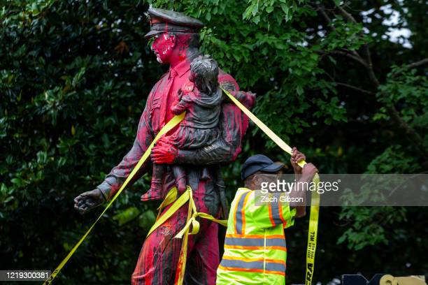 Workers remove a police memorial statue covered in red paint by protesters on June 11, 2020 in Richmond, Virginia. Protesters also tore down statues...