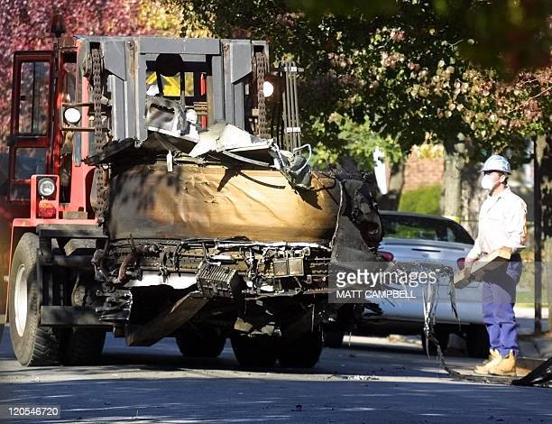 Workers remove a portion of the engine from American Airlines Flight 587 from behind a home 14 November 2001 in the Belle Harbor area of Queens New...