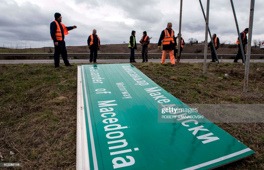 Workers remove a sign with the former name of the highway leading to the Greek border, 'Alexander of Macedonia', newly renamed 'Friendship Highway', near Skopje on February 21, 2018. The government decided to change the name of the highway, along with the name of the Skopje airport, following the name dispute with Greece. Athens has long objected to Macedonia's name, arguing it suggests Skopje has claims to the territory and heritage of Greece's historic northern region of the same name. / AFP PHOTO / Robert ATANASOVSKI