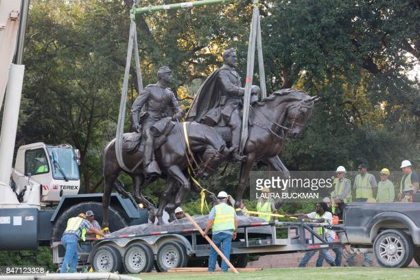 Workers remove a statue of a statue of Confederate general Robert E Lee from Robert E Lee Park in Dallas Texas on September 14 2017 Confederate...