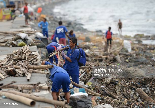 Workers remove debris washed ashore along the bay walk in Manila on October 30 as Typhoon Yutu made landfall north of the capital