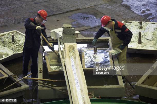 Workers remove impurities from cooling zinc ingots in the rotary foundry room at the Chelyabinsk Zinc Plant operated by Ural Mining and Metallurgical...