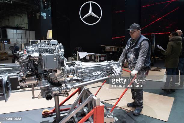Workers remove motor from Mercedes stand on February 28, 2020 at the Geneva International Motor Show which has been cancelled due to the Covid-19...