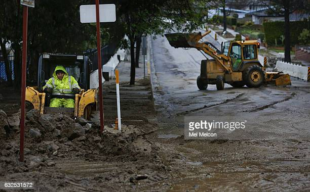 Workers remove mud and debris as a result of all the rain from the intersection of Deerlane Dr and Melcanyon Rd in Duarte January 23 2017