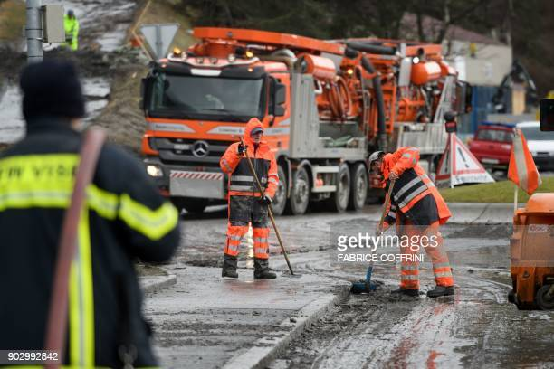 Workers remove mud and water after a mudslide in Eyholz near Visp on January 9 2018 Somes residents had to leave their homes in Eyhol after heavy...