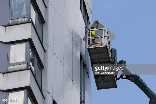 Workers remove panels of external cladding from the facade of Braithwaite House in London on July 3 in the wake of the Grenfell Tower fire...