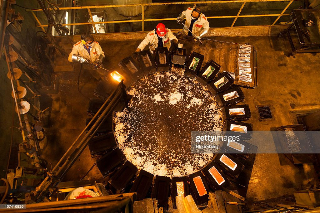 Workers remove shaped and cooled silver bullion bars from moulds at the KHGM Polska Miedz SA smelting plant in Glogow, Poland, on Monday, March 23, 2015. KGHM is the world's third-largest silver producer behind Fresnillo Plc and BHP Billiton Ltd. Photographer: Bartek Sadowski/Bloomberg via Getty Images