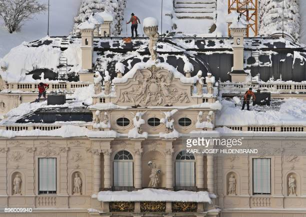 Workers remove snow from the roof of Linderhof Castle near Ettal southern Germany to protect it against damages on December 19 2017 / AFP PHOTO / dpa...