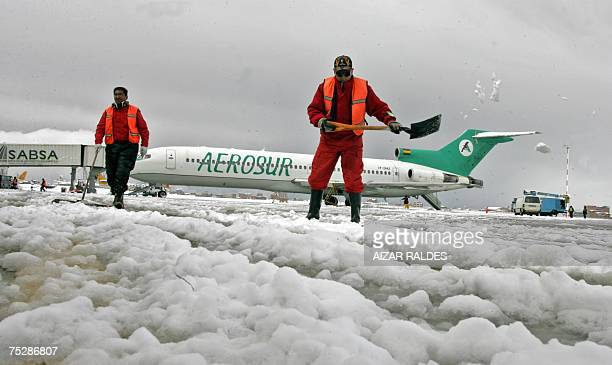 Workers remove snow from the tarmac of the El Alto airport 09 July 2007 in Bolivia Unexpected snowfalls struck the occidental part of Bolivia cutting...