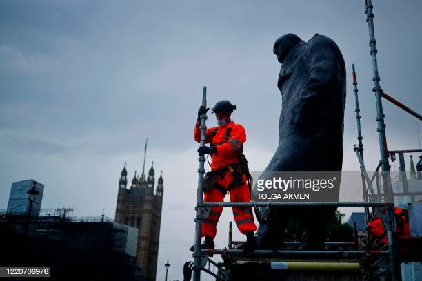 Workers remove the boards protecting the statue of former Prime Minister Winston Churchill from vandalism during anti-rascism portests, ahead of the...