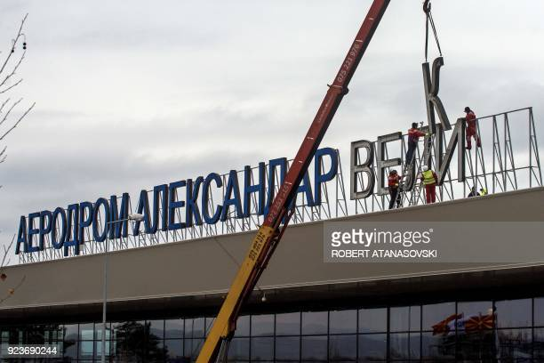 Workers remove the cyrillic letters of the airport name which is called Alexander the Great on the airport building on the outskirts of Skopje on...
