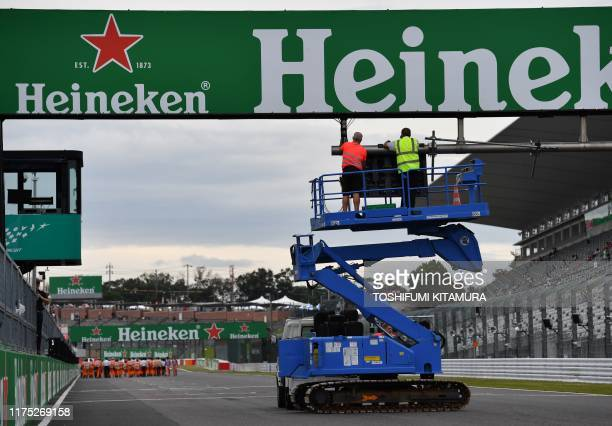 Workers remove the starting signal at the start and finish line to prepare for the approaching Typhoon Hagibis during the Formula One Japanese Grand...