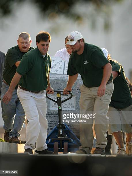 Workers remove the Ten Commandments monument from storage at the State Judicial Building July 19 2004 in Montgomery Alabama Ousted Alabama Chief...