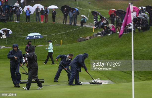 Workers remove the water flooding the green during the Evian Championship tournament on September 17 2017 in the French Alps town of EvianlesBains a...