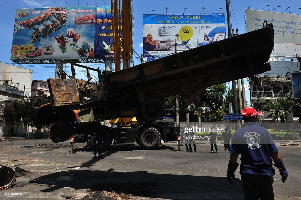 Workers remove the wreckage of a burnt truck from an intersection on Din Daeng in downtown Bangkok on May 21, 2010. Thailand picked up the pieces after violence and mayhem triggered by a crackdown on anti-government protests, as the focus swung to recovery and reconciliation in a divided nation. AFP PHOTO / Bay ISMOYO