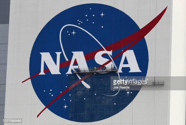 Workers repaint the NASA logo on the Vehicle Assembly Building at the Kennedy Space Center on May 28 2020 in Cape Canaveral Florida SpaceX's Crew...