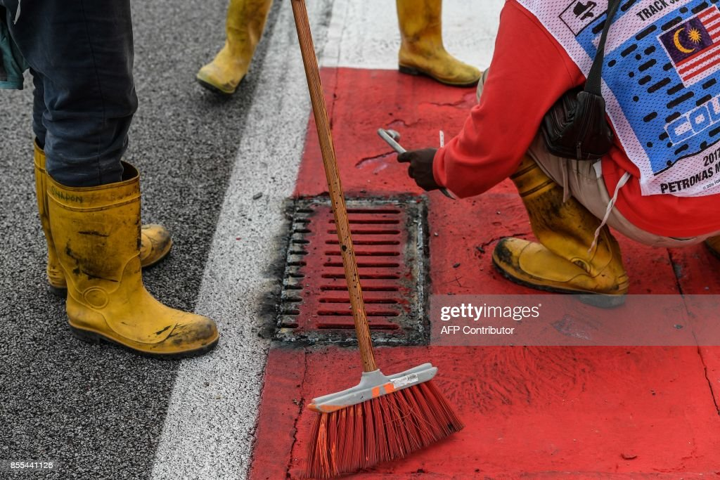 Workers repair a drain cover after Haas F1's French driver Romain Grosjean suffered a frightening tyre explosion during the second practice session of the Formula One Malaysia Grand Prix in Sepang on September 29, 2017. /