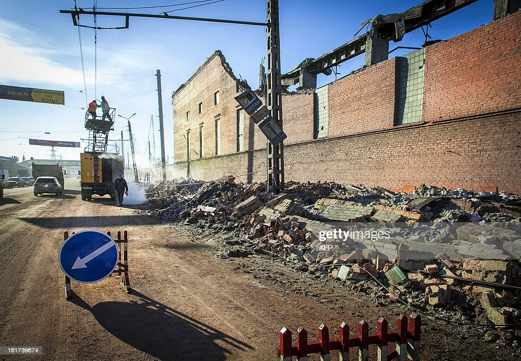 Workers repair a power line near the wall of a local zinc plant which was damaged by a shockwave from a meteor in the Urals city of Chelyabinsk, on February 15, 2013. A meteor strike in central Russia that left today hundreds of people injured is the biggest known human toll from a space rock, a British expert said.