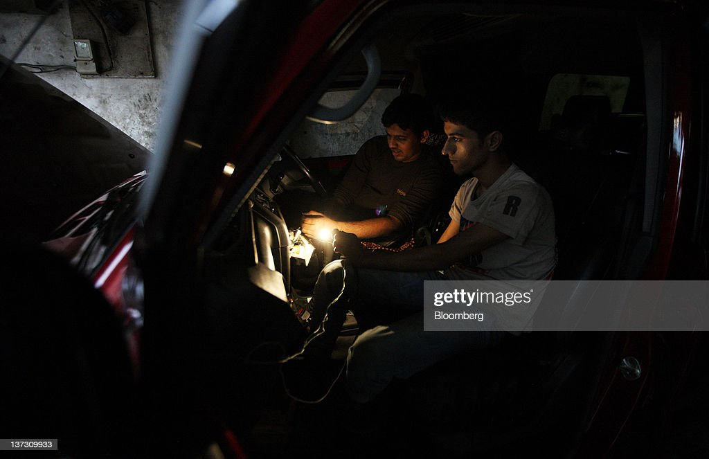 Workers repair a vehicle at a car dealership in Dhaka, Bangladesh, on Saturday, Jan. 7, 2012. Bangladesh's central bank this month raised interest rates for the second time in four months to curb inflation that has exceeded 9 percent since the start of 2011. Photographer: Tomohiro Ohsumi/Bloomberg via Getty Images