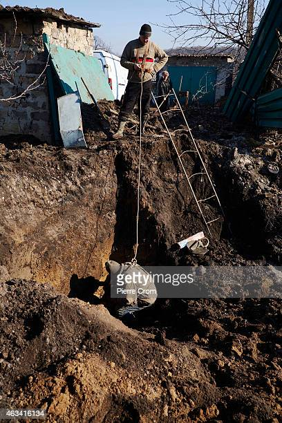Workers repair a water pipe as fighting in the area continues on February 14 2015 in Donetsk Ukraine Missiles fired from the direction of Ukrainian...