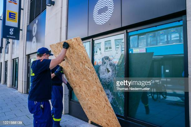 Workers repair damage to a display window of a shop following violent clashes between rioters and police that also led to looting the night before on...