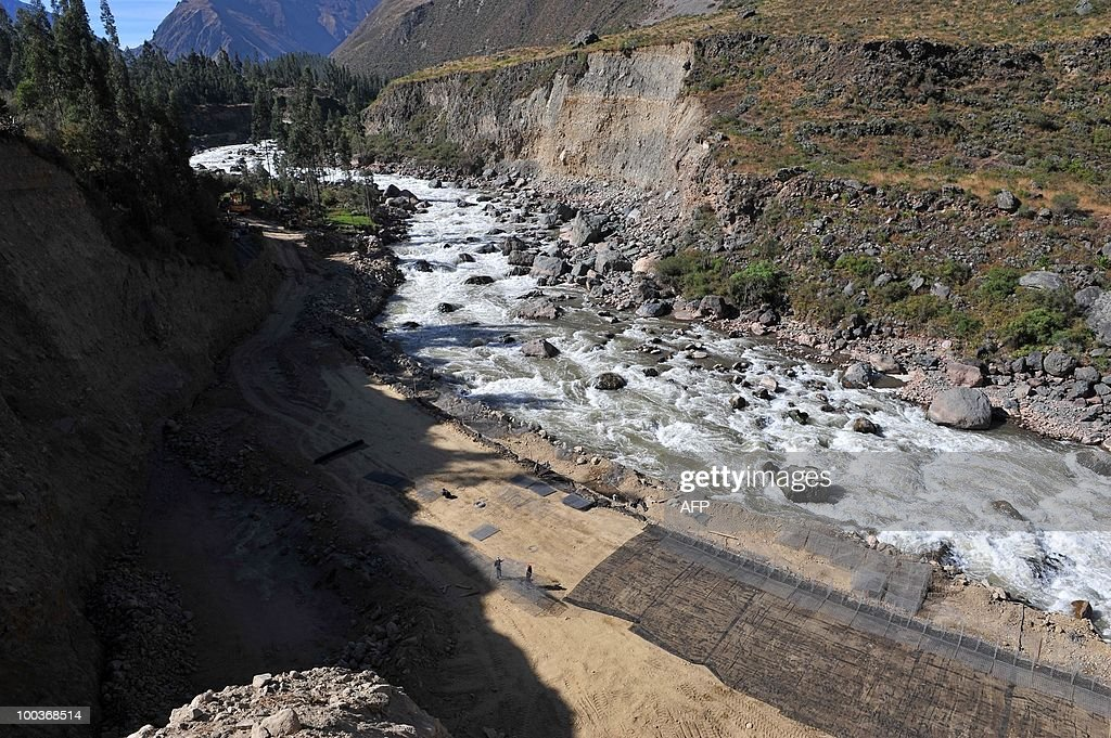Workers repair on May 23, 2010, a road carried away by the torrential Vilcanota River during the heavy rains that hit this area 1,200 kilometers southeast of Lima last January, isolating hundreds of tourists and collapsing the tourism industry for the city of Cuzco and the Inca fortress citadel of Machu Picchu during several weeks.