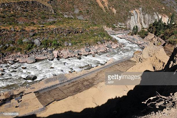 Workers repair on May 23 a road carried away by the torrential Vilcanota River during the heavy rains that hit this area 1200 kilometers southeast of...
