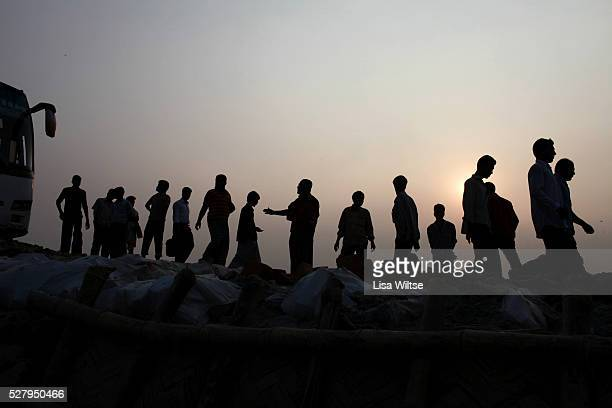Workers repair roads for trucks arriving on the ferry from Dhaka Trucks carrying rice jute sugar cane and fish from the west and southwest of the...