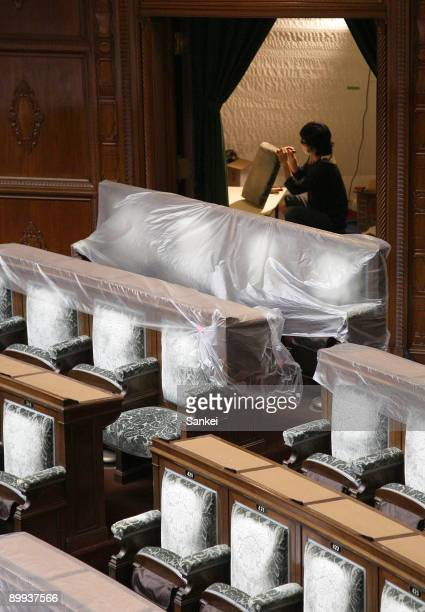 Workers repair the chairs in the House of Representatives on August 19 2009 in Tokyo Japan The upholstery of the chairs will be changed during the...
