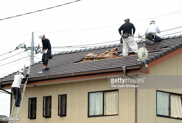 Workers repair the damaged roof a day after the blustery winds on June 16, 2015 in Isesaki, Gunma, Japan. The blustery winds overturned cars and two...