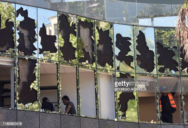 Workers repair the damages caused on the eve by demonstrators angry at the Chilean government in a building of a pensions fund in Santiago's...