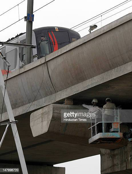 DMRC workers repair the most affected pillar of the Airport Express metro line near Buddha Jayanti Park on July 7 2012 in New Delhi India Airport...
