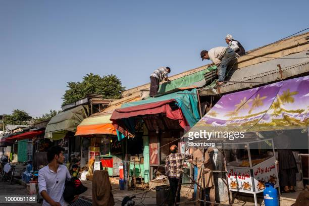 Workers repair the roof of a store at a market in Kabul Afghanistan on Thursday July 12 2018 US President Donald last year said 16000 US troops would...