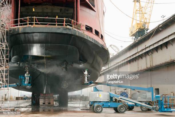 workers repairing ferry boat ship in dry dock - ship stock pictures, royalty-free photos & images
