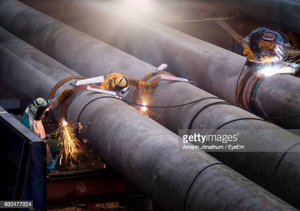 workers repairing pipes at factory - pipeline stock pictures, royalty-free photos & images