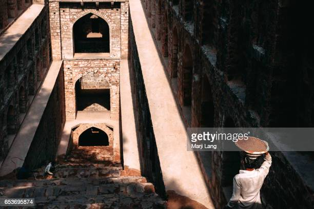 Workers repairing the Agrasen ki Baoli, an ancient step well which became protected monument by the Archaeological Survey of India. New Delhi, India.