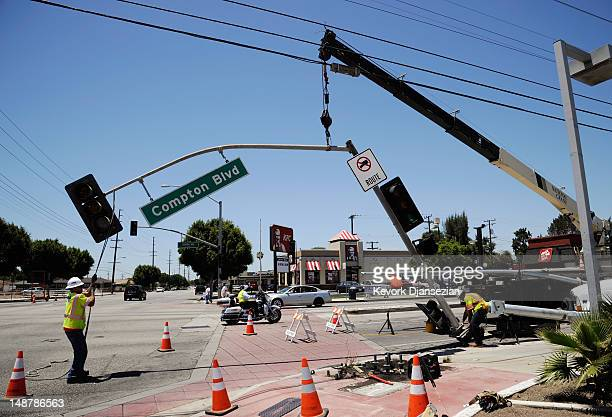 Workers replace a traffic signal on July 19 2012 in Compton California The City of Compton located south of Los Angeles with a population of nearly...