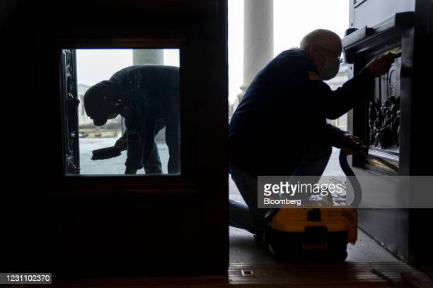 Workers replace a window that had been broken in the January 6 riots at the U.S. Capitol in Washington, D.C., U.S., on Thursday, Feb. 11, 2021. House...