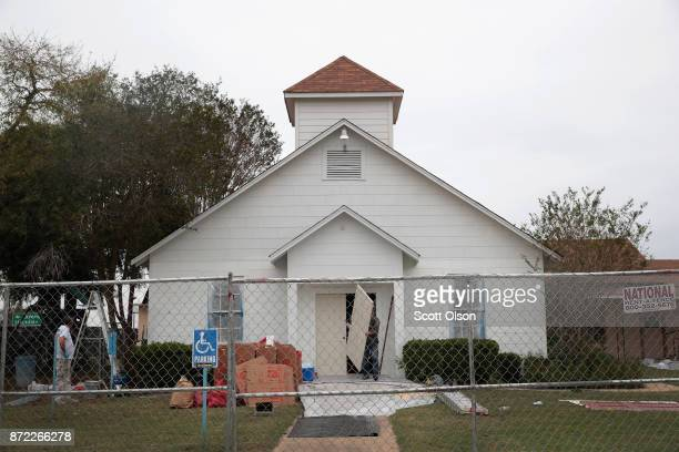 Workers replace the bulletscarred front door of the First Baptist Church of Sutherland Springs on November 9 2017 in Sutherland Springs Texas The...