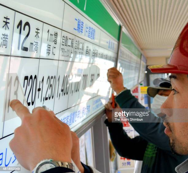 Workers replace to the new tariff board as the new 8 percent consumption tax launch at Sanport Ferry pier on March 31 2014 in Takamatsu Kagawa Japan...