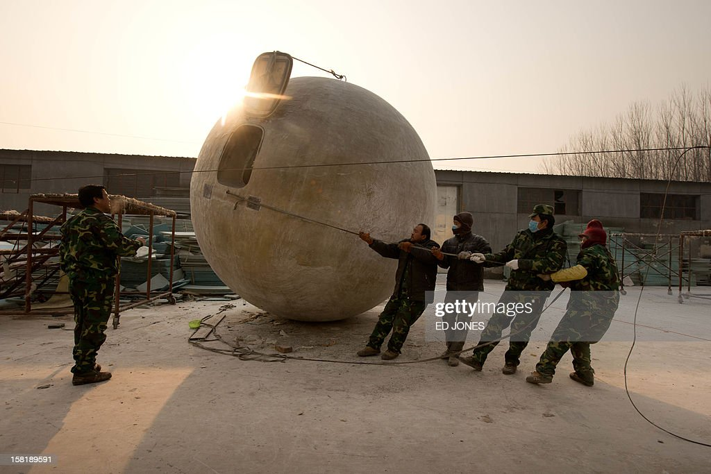 Workers reposition one of seven survival pods dubbed 'Noah's Arc' by creator, farmer Liu Qiyuan (L) in his yard at his home in the village of Qiantun, Hebei province, south of Beijing on December 11, 2012. Inspired by the apocalyptic Hollywood movie '2012' and the 2004 Asian tsunami, Liu hopes that his creations consisting of a fibreglass shell around a steel frame will be adopted by government departments and international organisations for use in the event of tsunamis and earthquakes. Liu has built seven pods which are able to float on water, some of which have their own propulsion. The airtight spheres with varying interiors contain oxygen tanks and seatbelts with space for around 14 people, and are designed to remain upright when in water. AFP PHOTO / Ed Jones