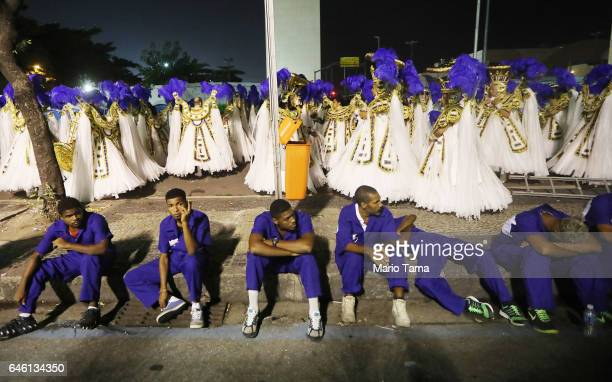 Workers rest as revelers from the Portela samba school wait to perform outside the Sambodrome in the early morning hours during Carnival festivities...