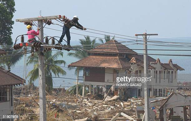 Workers restore power lines in Khao Lak tourist resort district 02 January 2005 in Phang Nga province southern Thailand after massive tsunami...