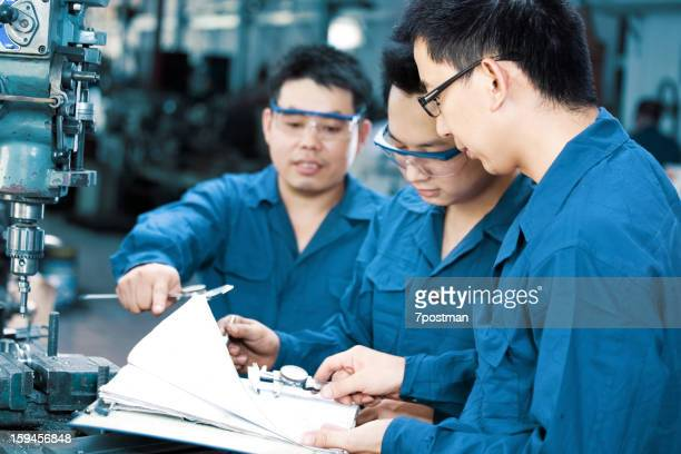 Workers reviewing blueprints in a factory