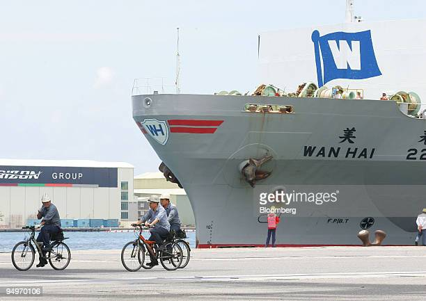 Workers ride bicycles at the port in Kaohsiung Taiwan on Thursday July 23 2009 Taiwan's export orders declined the least in eight months signaling...