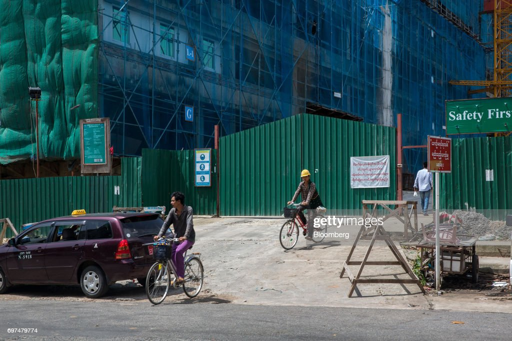 Workers ride bicycles while leaving a construction site in Yangon, Myanmar, on Monday, June 12, 2017. When the country opened to the outside world in 2011 after decades of military rule, the former British colony held promise as one of the worlds hottest tourist destinations, a last frontier for adventure travel. But it hasn't worked out that way. A construction glut has flooded Myanmar with unused hotel rooms, and poorly regulated building has damaged national treasures like the archaeological site of Bagan. Photographer: Taylor Weidman/Bloomberg via Getty Images