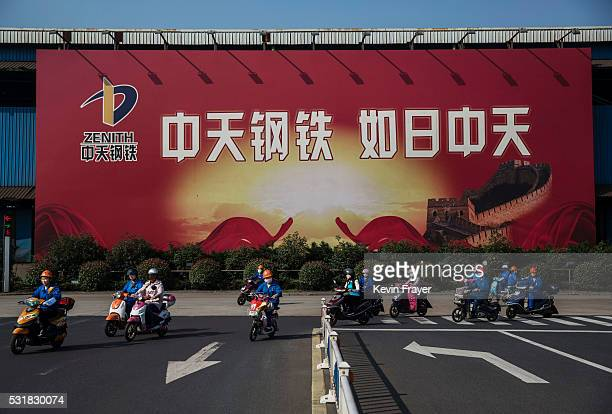 Workers ride past a sign saying 'Zhong Tian Steel Like the Sun at Noon' on their way to work at the Zhong Tian Steel Group Corporation on May 12 2016...