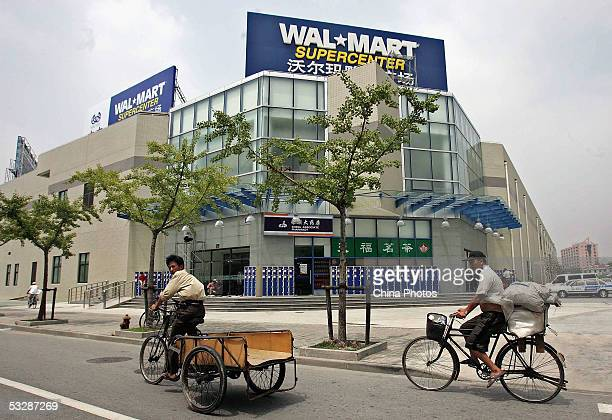Workers ride tricycles past the first WalMart store in Shanghai as preparations are made for the grand opening July 25 2005 in Shanghai China The...
