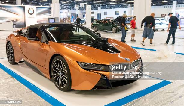 Workers right move car platforms past the new BMW i8 Roadster on Wednesday October 3 2018 in Anaheim in preparation for the start of the 2019model OC...
