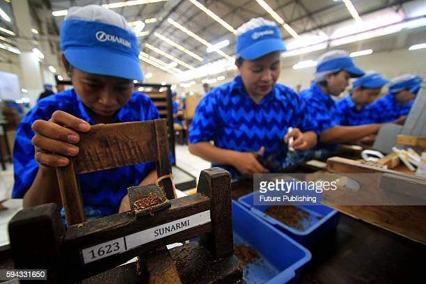 Workers roll clove cigarettes at a factory on August 22 2016 in Kudus Indonesia Indonesia is the fifth largest cigarette producing market with an...